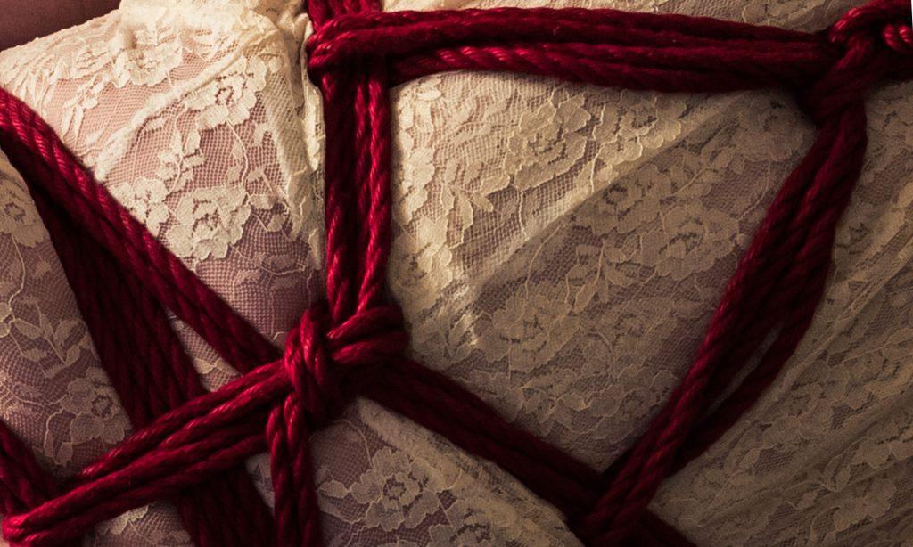 Shibari und fesseln, rotes Seil auf weißem Kleid